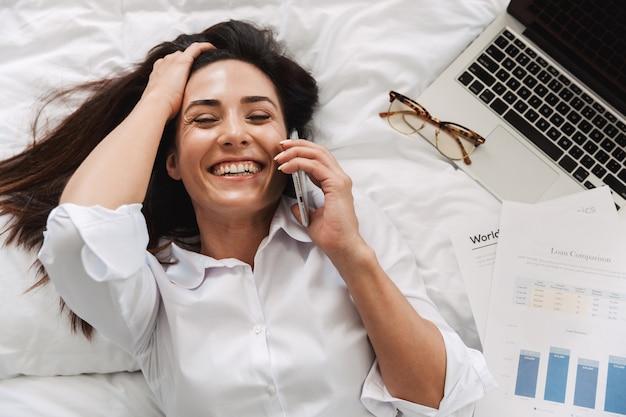 Verbazingwekkende mooie gelukkige jonge zakenvrouw in formele kleding binnenshuis thuis ligt op bed praten via de telefoon.