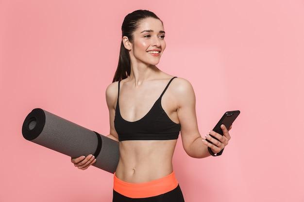 Verbazingwekkende mooie jonge mooie fitness vrouw met behulp van mobiele telefoon met tapijt geïsoleerd over roze muur