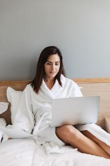 Verbazingwekkende mooie jonge zakenvrouw binnenshuis thuis met behulp van laptopcomputer.