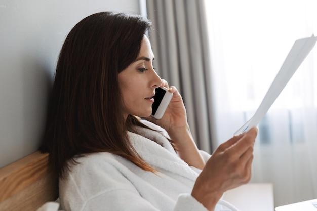 Verbazingwekkende mooie jonge zakenvrouw binnenshuis thuis met papier praten via de mobiele telefoon.
