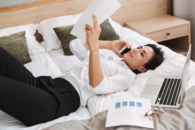 Verbazingwekkende mooie jonge zakenvrouw in formele kleding binnenshuis thuis ligt op bed praten via de telefoon met papieren documenten.