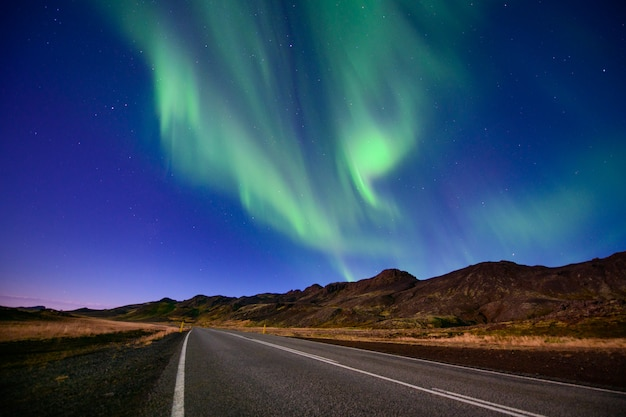 Verbazingwekkende noorderlicht, aurora borealis op lege weg in ijsland