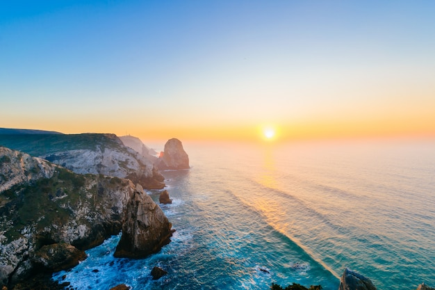Verbazingwekkende pittoreske zonsondergang boven zee en rotsen.