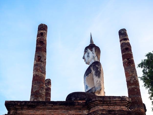 Verbazingwekkende scène van de wat mahathat-tempel in het district van het historische park sukhothai met een groot boeddhabeeld en een oude ancien-constructie, een unesco-werelderfgoed in thailand.