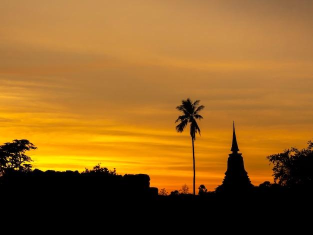 Verbazingwekkende scène van silhouet van pagode, tempel en gouden zonsonderganghemel in sukhothai historical park, een unesco-werelderfgoed in thailand.