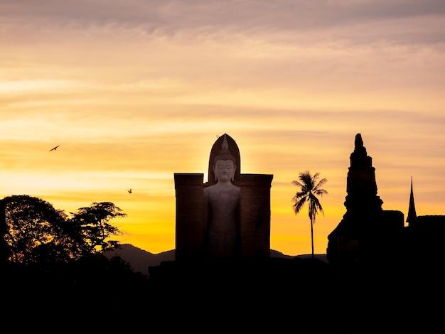 Verbazingwekkende scenetic van silhouet van wat mahathat temple in het district van sukhothai historical park met groot boeddhabeeld op gouden zonsondergang hemelachtergrond, een unesco world heritage site in thailand.