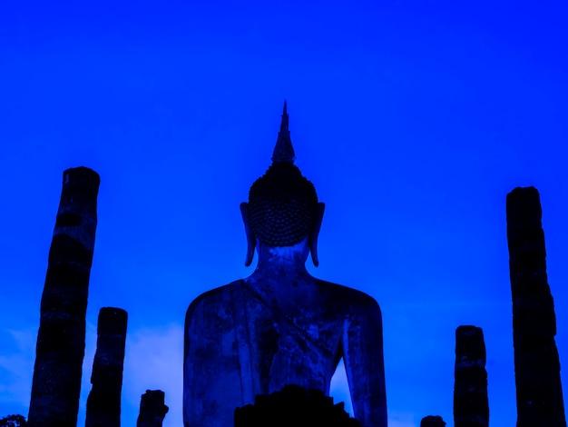 Verbazingwekkende scenetic van silhouet van wat mahathat temple in het district van sukhothai historical park met grote boeddhabeeld op blauwe avondrood achtergrond, een unesco world heritage site in thailand.