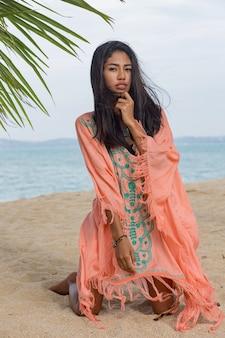 Verbazingwekkende sexy tan aziatische vrouw die zich voordeed op het tropische strand van het paradijs onder de pam-boom, zittend op wit zand, ontspannen en genieten van vakantie. boho jurk met borduursel. bali.
