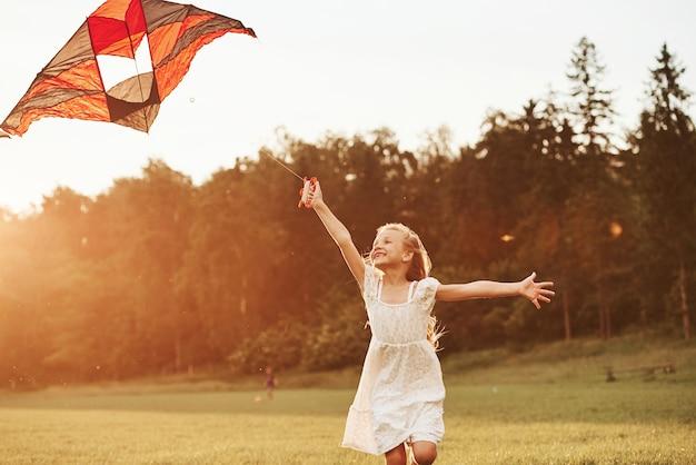Verbazingwekkende zonnestralen. gelukkig meisje in witte kleren veel plezier met vlieger in het veld. prachtige natuur.