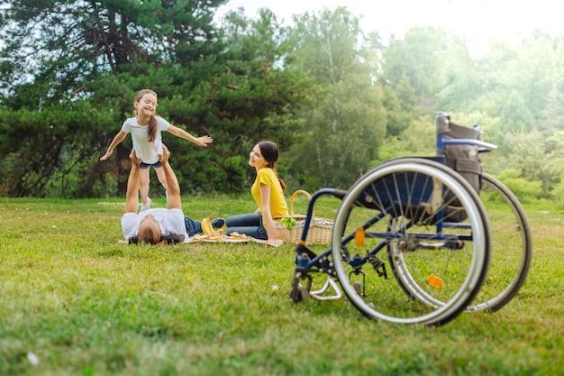 Verbeeldingskracht. gelukkig jonge man met een handicap liggend op het gras en zijn vrolijke dochter op te heffen als een vliegtuig terwijl zijn rolstoel op de voorgrond staat