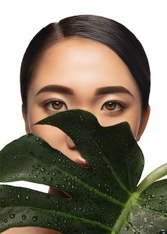 Verbergen. portret van mooie aziatische vrouw geïsoleerd op een witte studio achtergrond met groot monstera blad. schoonheid, mode, huidverzorging, cosmetica concept. verzorgde huid en frisse uitstraling. gezond, glanzend.