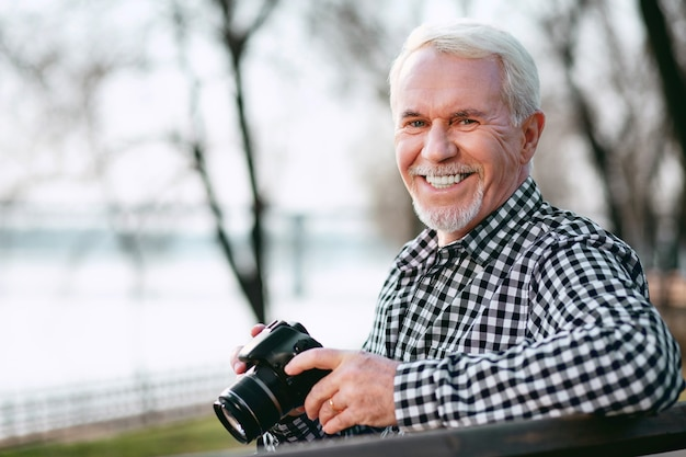 Verbeter je vaardigheden. vrolijke volwassen man met behulp van camera en grijnzend naar de camera
