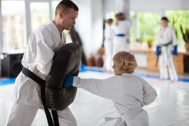 Verbetering van de kracht. jongen met krullend blond haar houdt van vechtsporten en verbetert zijn kracht