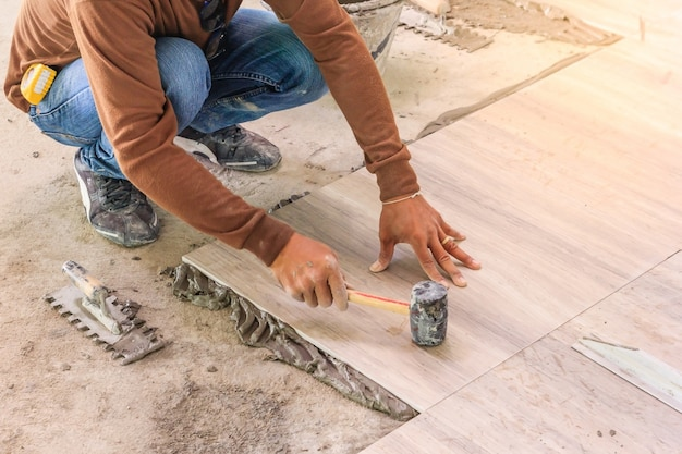 Verbetering van het huis, renovatie - bouwvakker tegelzetter is betegeling