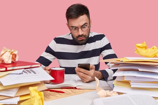 Verbijsterd emotionele jonge ongeschoren man houdt moderne cellulaire vast, draagt transparante ronde bril en gestreepte trui, drinkt aromatische hete koffie