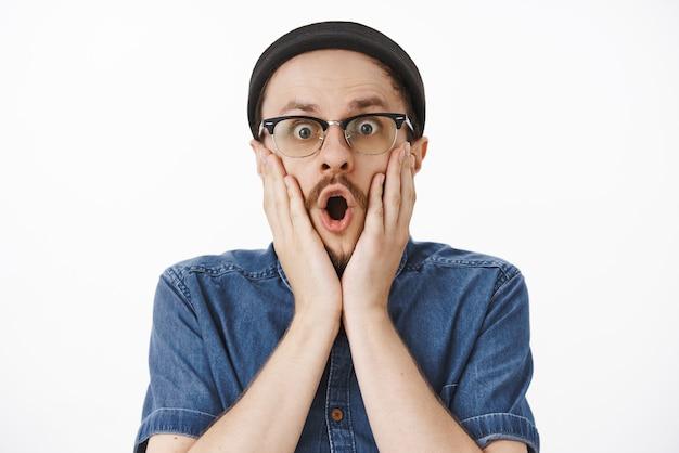 Verbijsterd en geschokt emotionele paniekerige man in beanie-bril en blauw shirt hand in hand op gezicht dichtbij geopend van verrassing mond starend bezorgd en geschud