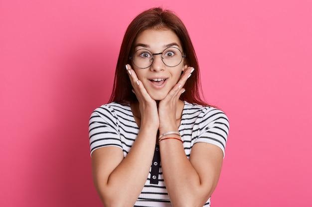 Verbijsterd en verbaasd meisje luistert naar roddels met opwinding en interesse, handpalmen op de wangen, poseert met verbaasde uitdrukking, staande over roze muur.
