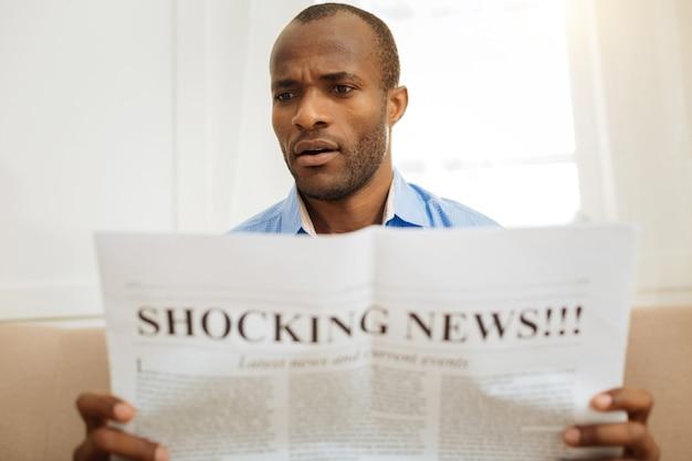 Verbijsterd. ernstige verbijsterde afro-amerikaanse man die een krant vasthoudt en leest terwijl hij op de bank zit