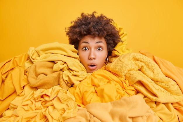 Verbijsterd krullend haar etnische vrouw met vast hoofd in stapel kleren koopt verschillende kledingstukken te koop in tweedehands kan niet geloven in zulke lage prijs poses tegen geel