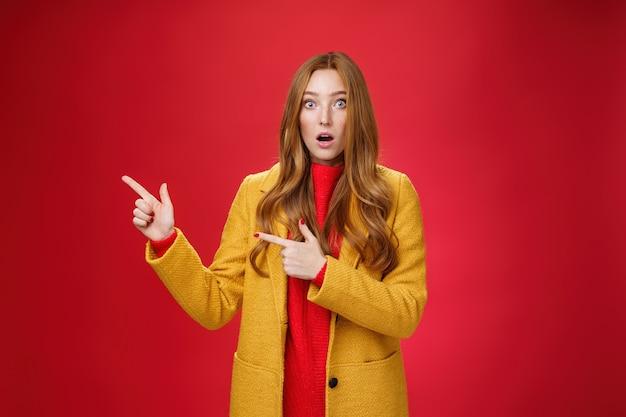 Verbijsterd sprakeloos en onder de indruk aantrekkelijke roodharige vrouw met sproeten in gele jas drop kaak verbaasd als knallende ogen op camera ondervraagd, wijzend naar links verbaasd over rode achtergrond.