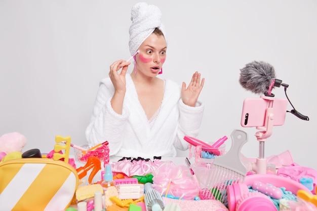 Verbijsterd vrouwelijk model maakt gebruik van cosmetische borstel en brengt vochtinbrengende pleisters onder de ogen aan