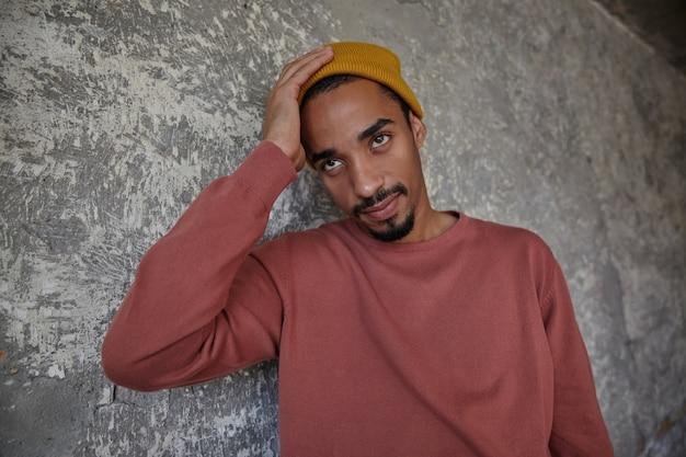 Verbijsterde aantrekkelijke bebaarde donkere man in roze trui en mosterdpet die de handpalm op zijn hoofd houdt terwijl hij over de betonnen muur staat, verward naar boven kijkend met gevouwen lippen