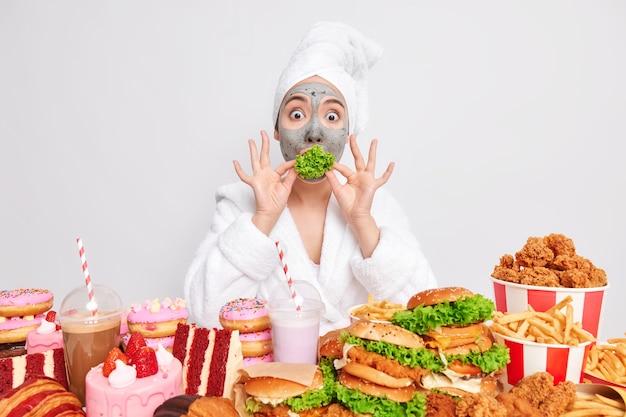 Verbijsterde aziatische vrouw houdt groene groente in mond en probeert gezond voedsel te eten