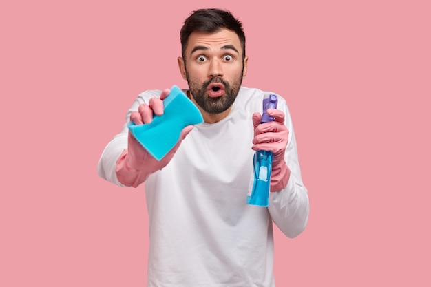 Verbijsterde bebaarde jonge kerel kijkt nauwgezet, ruimt de kamer op met schoonmaakspullen, heeft een geschokte uitdrukking, zorgt voor het huishouden