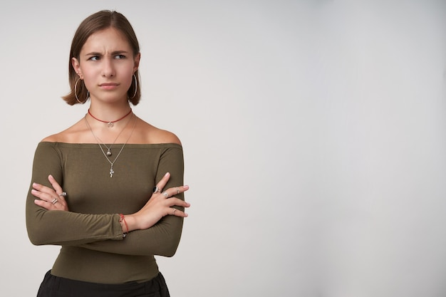 Verbijsterde donkerharige jongedame met kort kapsel die handen op haar borst vouwt terwijl ze verward opzij kijkt, gekleed in een olijfblouse terwijl ze poseert voor een witte muur