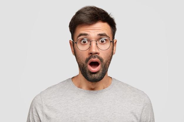 Verbijsterde emotionele bebaarde man houdt de mond wijd open, kijkt met ingehouden adem