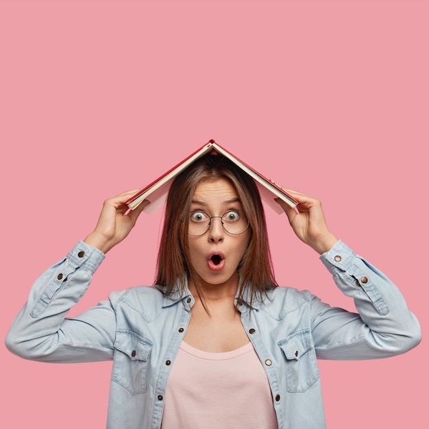 Verbijsterde emotionele studente houdt boek op zijn hoofd, geschokt omdat ze geen tijd heeft voor examenvoorbereiding, vraagt zich af om het nieuwe studiejaar te beginnen, gekleed in een spijkerblouse, poseert binnen. studeren concept