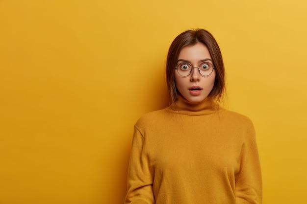 Verbijsterde emotionele vrouw verloor veel geld, staart sprakeloos en bezorgd, reageert zenuwachtig op een vreselijke situatie