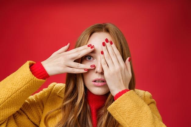 Verbijsterde en geschokte roodharige vrouw kan niet geloven wat voor vreselijks ze het gezicht ziet bedekken met de handpalmen open mond van schudde en glurend door vingers angstig en bang over rode achtergrond.