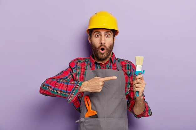 Verbijsterde handarbeider wijst naar reparatiegereedschap, bezig met wederopbouw, draagt helm, speciaal uniform. de verbaasde bouwvakker demonstreert bij het schilderen van penseel, aan het werk. vernieuwing