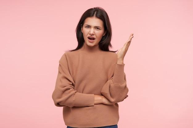 Verbijsterde jonge aantrekkelijke brunette vrouw gekleed in gebreide poloneck verhogen perplex haar handpalm terwijl ze naar de voorkant kijkt, geïsoleerd over roze muur