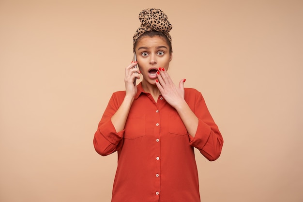 Verbijsterde jonge aantrekkelijke brunette vrouw met hoofdband versuft haar groene ogen afronden en emotioneel hand opheffen naar haar mond terwijl ze verrassend nieuws aan de telefoon hoort