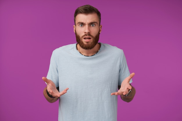 Verbijsterde jonge bebaarde man met met trendy kapsel handpalmen verward en fronsende wenkbrauwen verhogen, poseren op paars in vrijetijdskleding