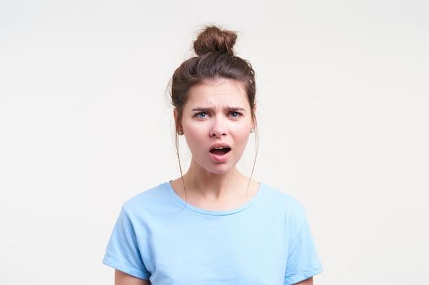 Verbijsterde jonge blauwogige mooie brunette vrouw met casual kapsel grimassen haar gezicht terwijl ze verward naar voren kijkt, geïsoleerd over witte muur
