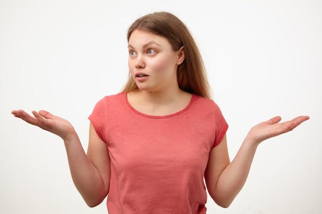 Verbijsterde jonge blonde vrouw met natuurlijke make-up die verwonderd opzij kijkt en handpalmen omhoog houdt terwijl ze op een witte achtergrond in een roze t-shirt staat