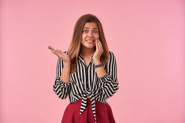 Verbijsterde jonge bruinharige brunette vrouw die verward handpalm opheft en haar tanden laat zien terwijl ze beschaamd kijkt, staande tegen roze
