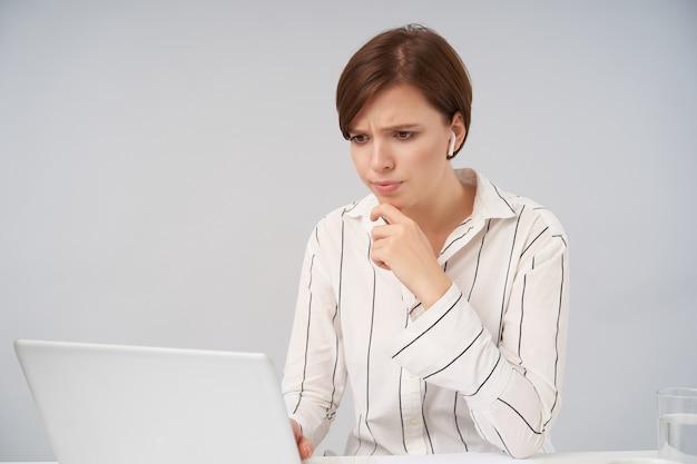 Verbijsterde jonge bruinharige dame met natuurlijke make-up die kin met opgeheven hand en fronsende wenkbrauwen vasthoudt terwijl ze peinzend naar het scherm van haar laptop kijkt, geïsoleerd op wit