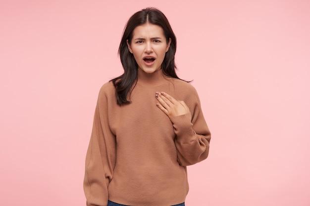 Verbijsterde jonge bruinharige dame met natuurlijke make-up fronst haar wenkbrauwen en houdt de handpalm op haar borst terwijl ze verward naar voren kijkt, geïsoleerd over roze muur
