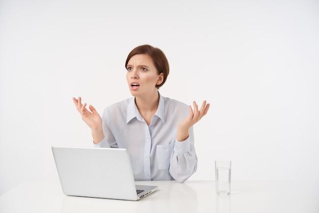 Verbijsterde jonge bruinharige mooie vrouw met casual kapsel fronst haar wenkbrauwen en verhoogt verward handpalmen terwijl ze opzij kijkt, zittend aan tafel op wit