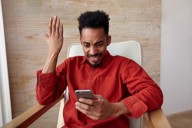 Verbijsterde jonge, gekrulde, bebaarde donkere man die emotioneel zijn hand opheft en verwarrende wenkbrauwen fronst terwijl hij op het scherm van zijn mobiele telefoon kijkt, geïsoleerd op het interieur