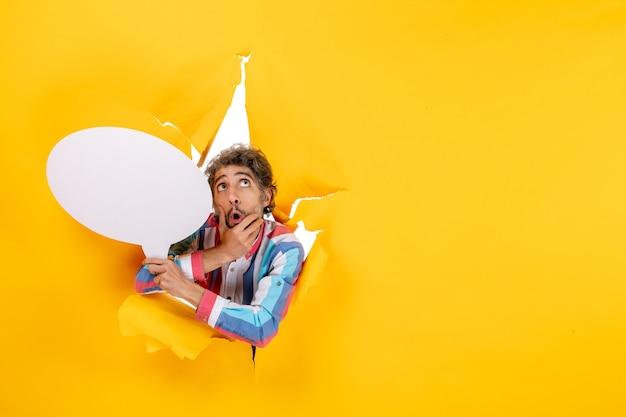 Verbijsterde jonge kerel die een witte ballon vasthoudt en omhoog kijkt in een gescheurd gat en een vrije achtergrond in geel papier