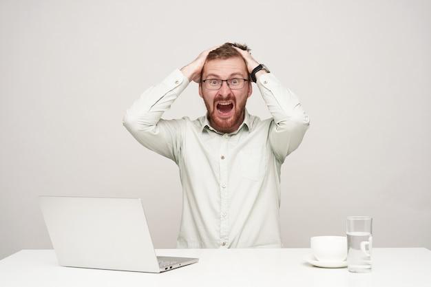 Verbijsterde jonge knappe bebaarde man in brillen zijn hoofd geklemd met opgeheven handen terwijl hij verbaasd naar de camera kijkt met gestrest gezicht, geïsoleerd op witte achtergrond