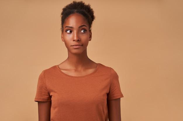 Verbijsterde jonge mooie bruinogige krullende brunette vrouw met donkere huid die haar mond draait terwijl ze verwonderd opzij kijkt, geïsoleerd op beige