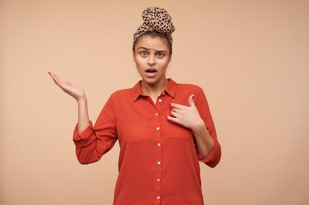 Verbijsterde jonge mooie brunette dame met natuurlijke make-up die zichzelf laat zien en de handpalm omhoog houdt terwijl ze verward naar voren kijkt, staande over de beige muur