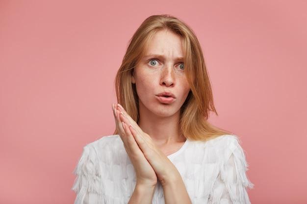 Verbijsterde jonge mooie vrouw met casual kapsel fronsende wenkbrauwen terwijl ze verward naar de camera kijkt, staande over roze achtergrond met opgeheven gevouwen handpalmen