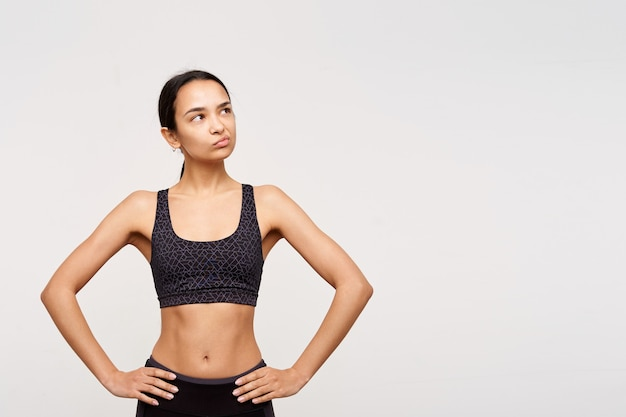 Verbijsterde jonge slanke donkerharige vrouw zonder make-up houdt haar handen op de taille en kijkt peinzend opzij, staande over een witte muur in sportieve kleding